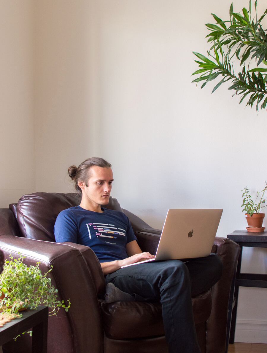 Web developer Émile Perron working in his living room